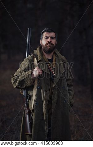 A Bearded Serious Male Hunter In A Long Green Cloak With A Hunting Rifle On His Shoulder And Cartrid