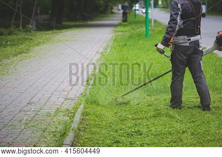 A Worker In Protective Clothing And Gloves With A Lawn Mower Walks Along The Lawn Nearby Along The W
