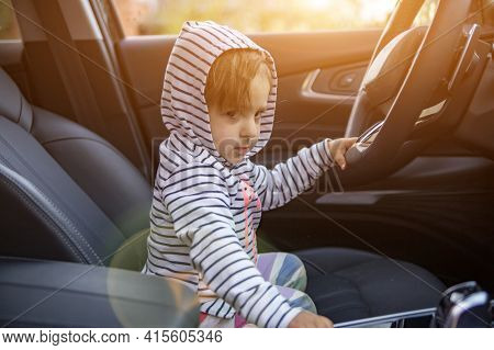 Cute Toddler Plays Driver In Parents Modern Car. Adorable Child Explore Drivers Sear Of Premium Car.