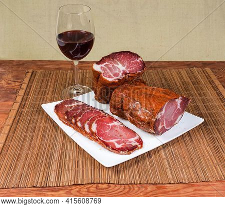 Partly Sliced Dry-cured Pork Neck On The Square White Dish And Glass Of Red Wine On Bamboo Table Mat