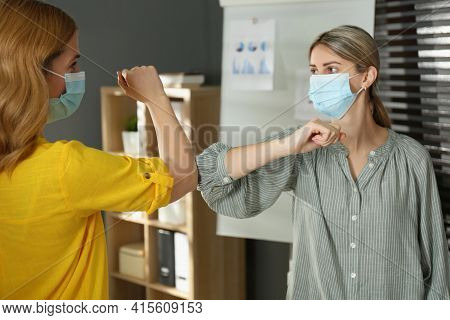 People Greeting Each Other By Bumping Elbows Instead Of Handshake Indoors