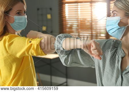 People Greeting Each Other By Bumping Elbows Instead Of Handshake Indoors, Closeup