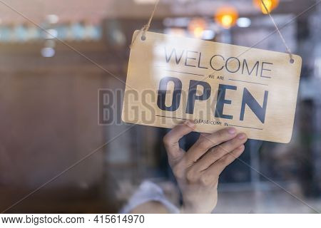 Hand Of Asian Owner Retail ,coffee Shop Woman Turning Sign Board To Open. Protection To Pandemic Of