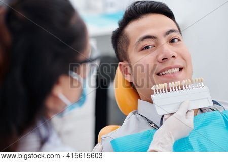 Dentist Using Special Palette When Choosing Teeth Color Of Smiling Male Patient Before Whitening Pro