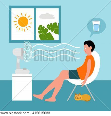 Man Sitting In His House In Front Of An Electric Fan. He Exhausted Of Hot Summer Day. Sweaty And Thi