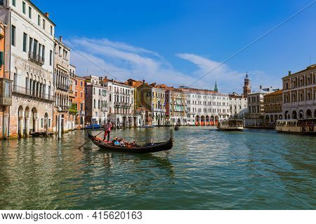 VENICE, ITALY - AUGUST 21, 2016: Tourists ride in gondola in Grand Canal on August 21, 2016 in Venice Italy.