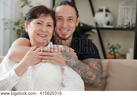 Portrait Of Cheerful Hugging Mixed-race Mother And Son Spending Weekend Together At Home Due To Pand