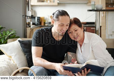 Cheerful Mixed-race Mature Mother And Her Adult Son Spending Time Together And Looking At Photos In