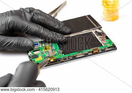 Close-up Of Electronics Repairs. Electronics Repair Soldering Of Microchips And Printed Circuit Boar