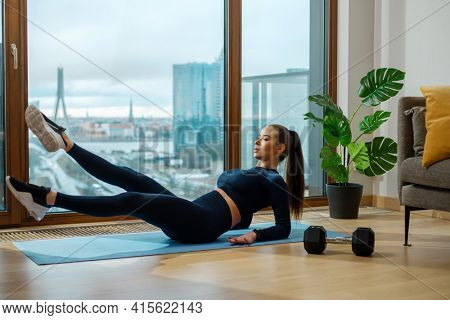 Slim brunette woman with brown hair practices abdominal exercises near panoramic window with view on city in summer in room