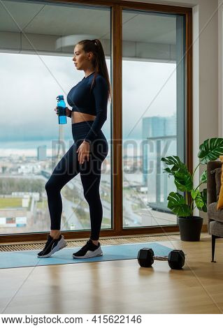 Slim brunette stands with water bottle in hand by pot plant and panoramic window with view on city in spring on glazed balcony
