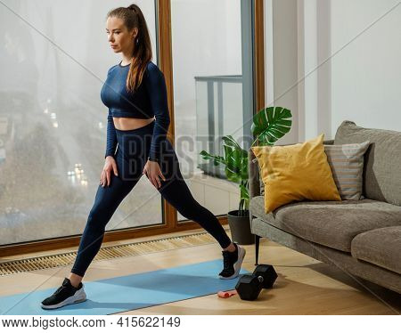 Slim young brunette in turquoise jumpsuit takes big step on blue mat near window against sofa with green pot plant in room