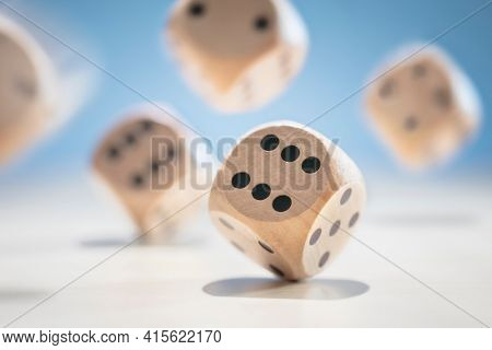 Throwing and rolling many wooden dice on a blue background