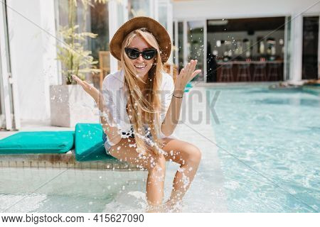 Charming Fair-haired Girl In Sunglasses Fooling Around During Photoshoot With Water. Outdoor Portrai