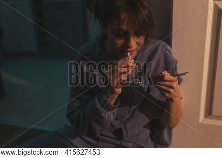 Female Drug Addict Sitting On The Kitchen Floor In The Dark, Preparing Her Next Intravenous Heroin D