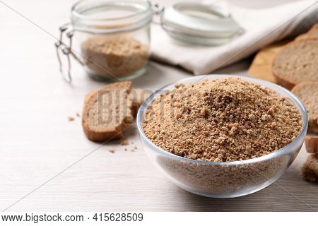 Fresh Breadcrumbs In Bowl On White Wooden Table. Space For Text