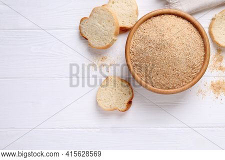 Fresh Breadcrumbs In Bowl On White Wooden Table, Flat Lay. Space For Text