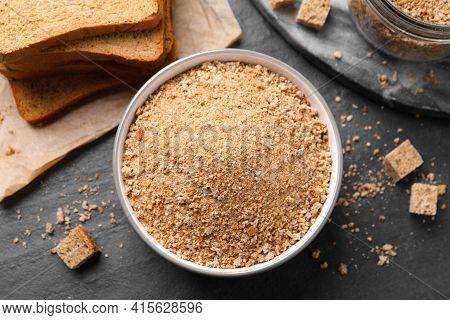 Fresh Breadcrumbs In Bowl On Black Table, Flat Lay