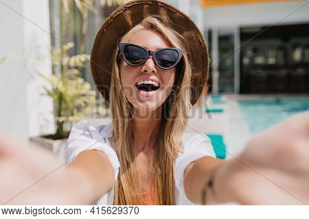 Blissful Blonde Woman In Glamorous Sunglasses Expressing Positive Emotions. Outdoor Shot Of Excited