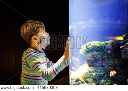 Kid Boy Wearing Medical Mask And Visiting Zoo Aquarium. Happy Baby Child Watching Fishes And Jellyfi