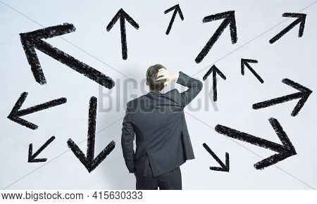 Businessman Standing Confused In Front Of A White Background With Black Arrows, Choice And Path Dile