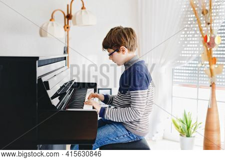 School Boy With Glasses Playing Piano In Living Room. Child Having Fun With Learning To Play Music I