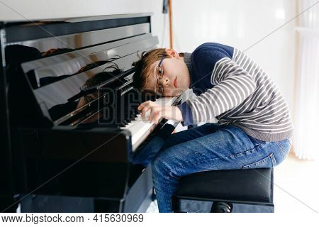 Frustrated Sad Boy With Glasses Playing Piano In Living Room. Lonely Child Learning To Play Music In