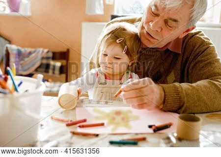 Cute Little Baby Toddler Girl And Handsome Senior Grandfather Painting With Colorful Pencils At Home