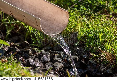 Clean Water Flows Through A Plastic Chute. Water For Watering Plants.