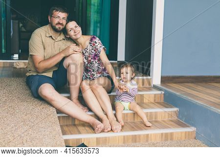 Family With Children Sit On Steps Leading Up To Porch Of Home. Happy Parents With Toddler Girl Daugh