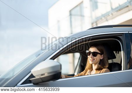 Young Woman In Sunglasses Left The House And Driving A Car. Businesswoman Going To Work From The Hou