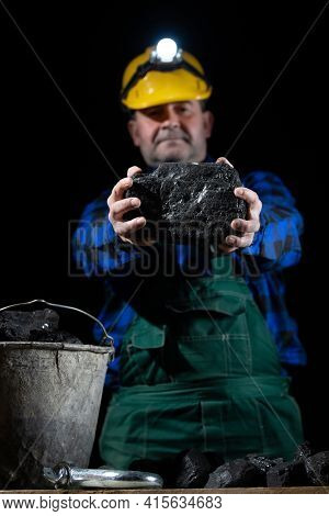 A Miner Holds A Large Lump Of Coal In His Hands And A Bucket Full Of Coal Stands Next To Him. A Helm