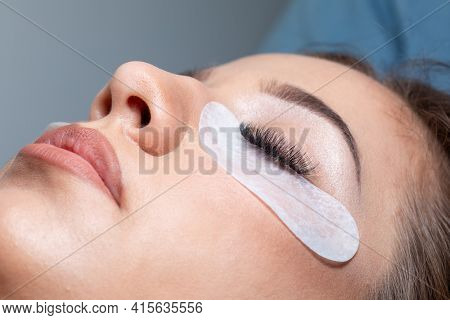 Treatment of Eyelash Extension. Lashes. Eyes with Long Eyelashes and under eye mask cosmetic patch.