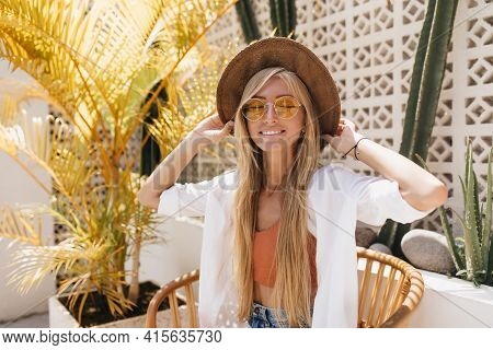 Pretty Fair-haired Girl Smiling With Eyes Closed Near Exotic Palm Tree. Outdoor Photo Of Relaxed Fem