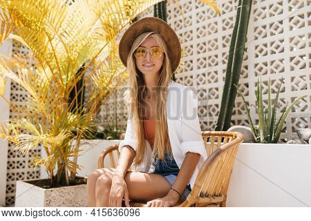 Elegant Young White Woman In Hat Sitting In Resort Cafe. Outdoor Portrait Of Stunning Long-haired Bl