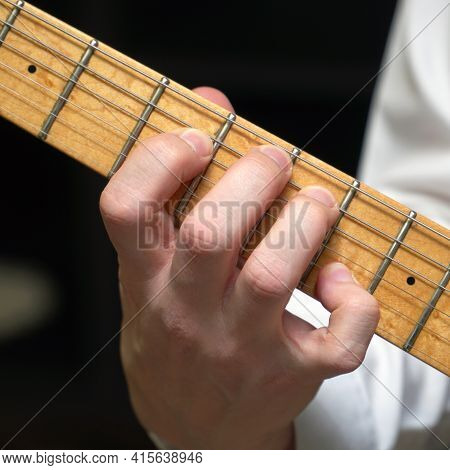 Guitarists Fingers On The Neck Of A Six-string Electric Guitar