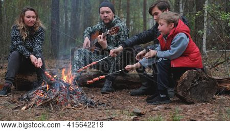 Father is playing guitar while his children and wife frying a meat. Family sits around a campfire. Children with parents are resting in the woods. Family frying sausages over a fire in woods.