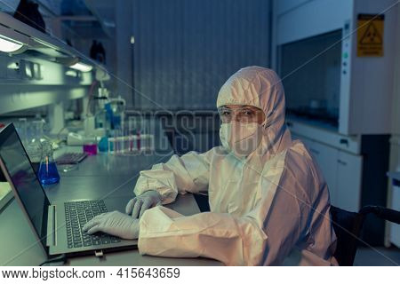 Portrait of mature woman in protective workwear looking at camera while typing on laptop at the table in the lab