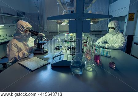 Two colleagues in protective workwear sitting at the table and working with chemical samples in test tubes in the laoratory