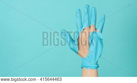 Hand Wearing Torn Medical Gloves Or Torn Rubber Gloves On Blue And Green  Or Tiffany Blue Color Back