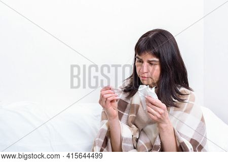 Sick Day At Home. A Sick Woman Blows Her Nose Into A Paper Handkerchief, Blows Her Nose And Holds Th
