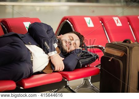 Tired middle aged businessman in formalwear lying on row of red leather seats and napping in lounge of modern airport while waiting for flight