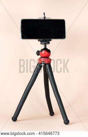 A Red-and-black Desktop Phone Tripod Stands On A Pink Background. Space For Photos And Text. Tripod