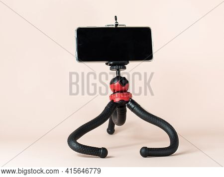 A Desktop Tripod With A Smartphone Attached To It Stands On A Light Background. Ease Of Communicatio