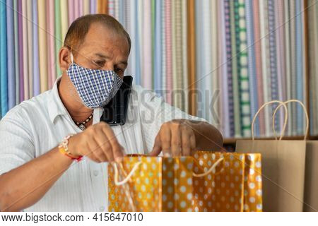 Shopkeeper With Medical Face Mask Checking Ordered Bags Before Handover To Customer - Concept Of Ord