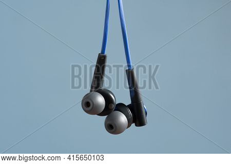 Headphone Hanging On A Light Blue Background Concept