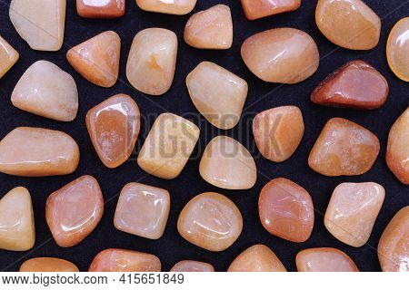Red Aventurine Rare Jewel Texture On Black Background. Sparse Mineral Pebbles Backdrop.