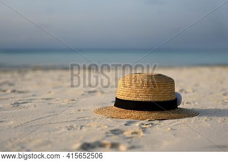 Women's Straw Hat With Black Ribbon Is Lying On The White Sand On The Beach,blue Sea And Blue Sky In
