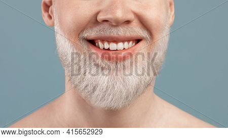 Cropped Portrait Of Albino Man With Wide Beaming Smile And Healthy Teeth, Over Turquoise Studio Back