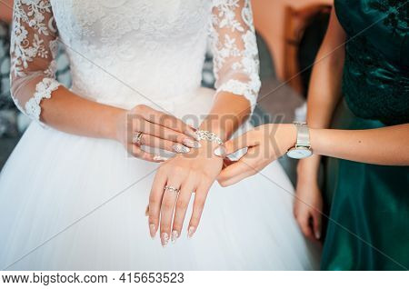 Bridesmaid Helps To Wear Bracelet On The Brides Hand